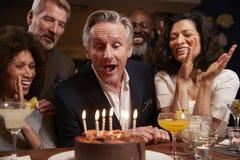 Grupo de amigos envelhecidos meio que comemoram o aniversário na barra imagens de stock royalty free