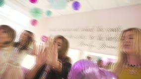 Grupo de amigos fêmeas atrativos novos felizes entusiasmado que têm a dança do divertimento que comemora a festa de anos no salão video estoque