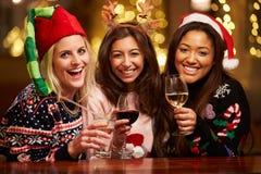 Grupo de amigos fêmeas que apreciam bebidas do Natal na barra Fotos de Stock Royalty Free