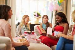 Grupo de amigos fêmeas que encontram-se para a festa do bebê em casa fotografia de stock