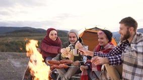 Grupo de amigos felices clining por la botella de cerveza mientras que cocina las salchichas en el fuego en la montaña metrajes