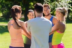 Grupo de amigos felices con las manos en el top al aire libre Imágenes de archivo libres de regalías