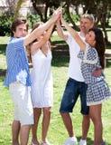 Grupo de amigos felices con los brazos levantados Fotografía de archivo