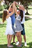 Grupo de amigos felices con los brazos levantados Foto de archivo libre de regalías