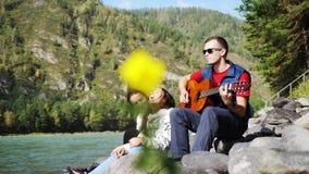 Grupo de amigos felices en la playa que toca la guitarra en un día de verano al lado del río de la montaña Foto de archivo libre de regalías