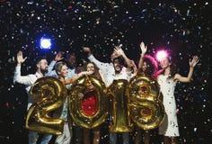 Grupo de amigos felices jovenes con los globos del número en el partido del Año Nuevo Imagenes de archivo