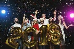 Grupo de amigos felices jovenes con los globos del número en el partido del Año Nuevo Fotos de archivo