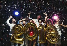 Grupo de amigos felices jovenes con los globos del número en el partido del Año Nuevo Fotos de archivo libres de regalías