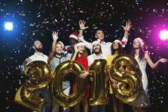 Grupo de amigos felices jovenes con los globos del número en el partido del Año Nuevo Imagen de archivo libre de regalías