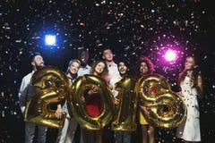 Grupo de amigos felices jovenes con los globos del número en el partido del Año Nuevo Imagen de archivo