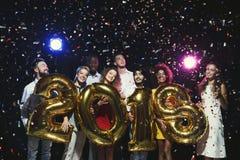 Grupo de amigos felices jovenes con los globos del número en el partido del Año Nuevo Imágenes de archivo libres de regalías