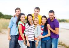 Grupo de amigos felices que abrazan en la playa Fotografía de archivo libre de regalías