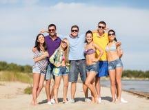 Grupo de amigos felices que abrazan en la playa Imágenes de archivo libres de regalías