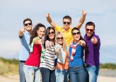 Grupo de amigos felices que abrazan en la playa Fotografía de archivo