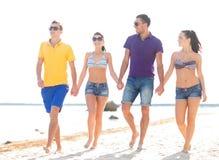Grupo de amigos felices que caminan a lo largo de la playa Fotografía de archivo libre de regalías