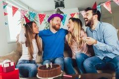 Grupo de amigos felices que celebran cumpleaños en casa y que se divierten imagen de archivo