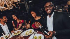 Grupo de amigos felices que hacen frente y que cenan imagen de archivo