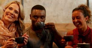 Grupo de amigos felices que obran recíprocamente mientras que comiendo café en el restaurante 4K 4k metrajes