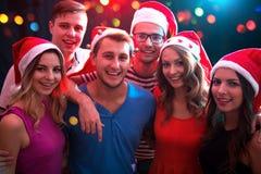 Grupo de amigos felices que presentan en los sombreros de Papá Noel imagen de archivo