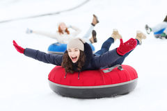 Grupo de amigos felices que resbalan abajo en los tubos de la nieve Fotos de archivo libres de regalías
