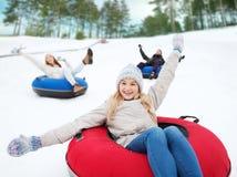 Grupo de amigos felices que resbalan abajo en los tubos de la nieve Imagen de archivo
