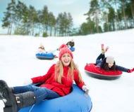 Grupo de amigos felices que resbalan abajo en los tubos de la nieve Foto de archivo