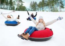 Grupo de amigos felices que resbalan abajo en los tubos de la nieve Foto de archivo libre de regalías