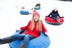 Grupo de amigos felices que resbalan abajo en los tubos de la nieve Fotografía de archivo