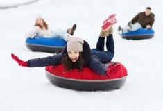 Grupo de amigos felices que resbalan abajo en los tubos de la nieve Fotografía de archivo libre de regalías