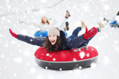 Grupo de amigos felices que resbalan abajo en los tubos de la nieve Imagen de archivo libre de regalías