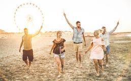 Grupo de amigos felices que se divierten en la playa en la puesta del sol Imagenes de archivo