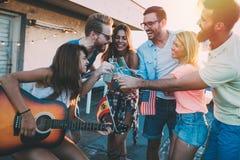 Grupo de amigos felices que tienen partido en tejado Fotografía de archivo
