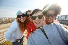 Grupo de amigos felices que toman el selfie en la calle Imagen de archivo