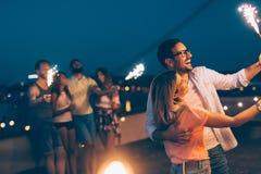 Grupo de amigos felizes que comemoram no telhado fotos de stock