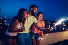Grupo de amigos felizes que comemoram no telhado imagens de stock royalty free
