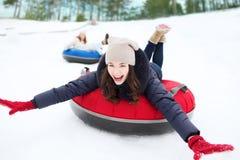 Grupo de amigos felizes que deslizam para baixo nos tubos da neve Foto de Stock