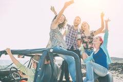 Grupo de amigos felizes que fazem o partido em um jovem automobilístico do jipe que come o champanhe bebendo do divertimento e qu foto de stock royalty free