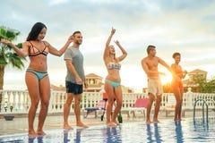 Grupo de amigos felizes que fazem uma festa na piscina no por do sol - jovem que tem o divertimento que dança ao lado da associaç imagens de stock