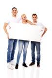 Grupo de amigos felizes que guardam a bandeira vazia Fotografia de Stock