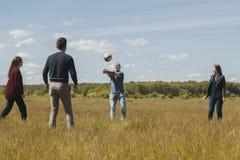Grupo de amigos felizes que jogam o voleibol no campo do verão Imagens de Stock Royalty Free