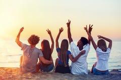 Grupo de amigos felizes que t?m o divertimento na praia do oceano no alvorecer imagens de stock royalty free