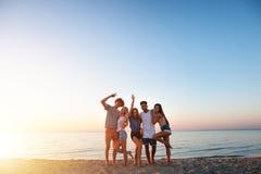 Grupo de amigos felizes que t?m o divertimento na praia do oceano no alvorecer fotos de stock royalty free