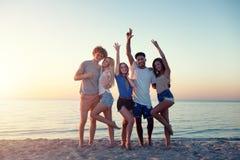 Grupo de amigos felizes que t?m o divertimento na praia do oceano no alvorecer fotos de stock