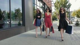 Grupo de amigos femeninos atractivos que caminan en la ciudad que muestra sus compras metrajes