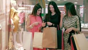 Grupo de amigos femeninos felices que discuten la ropa que ella ha visto en la tienda almacen de metraje de vídeo