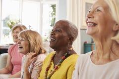 Grupo de amigos femeninos mayores que se relajan en Sofa At Home foto de archivo