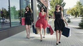 Grupo de amigos femeninos preciosos que caminan abajo de la calle después de un día de las compras metrajes