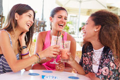 Grupo de amigos femeninos que beben los cócteles en la barra al aire libre Imagen de archivo libre de regalías
