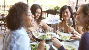 Grupo de amigos femeninos que disfrutan de la comida en el restaurante al aire libre metrajes