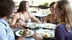 Grupo de amigos femeninos que disfrutan de la comida en el restaurante al aire libre almacen de metraje de vídeo